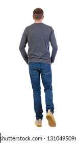 Back view of going  handsome man . walking young guy . Rear view people collection. Isolated over white background. A young guy in a gray sweater slowly goes forward with his hands in his pockets.
