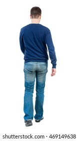 Back view of going  handsome man. walking young guy . Rear view people collection.  backside view of person.  Isolated over white background. bearded man in blue pullover slowly moves forward.