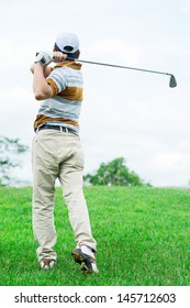 Back view of a golfer playing golf on the loan