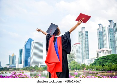 back view of graduate student asian woman hug future and look up to copy space, she wear graduation cap and gown