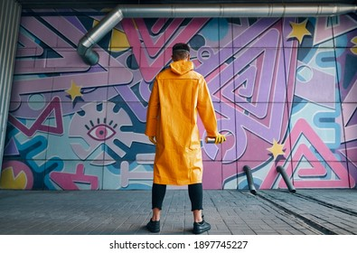 Back view of graffiti painter looking to the wall with his paintings. Street art concept