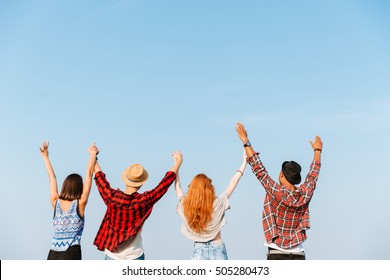 Back view of group of four young people standing and holding raised hands over blue sky background