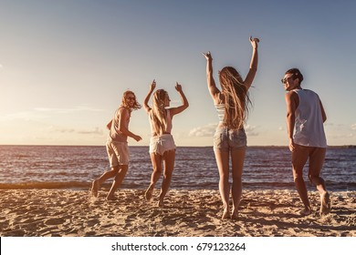 Back view of group of young attractive friends are having fun on beach, running and smiling on sunset.