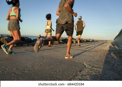 Back view of a group of young sporty friends jogging together outdoors
