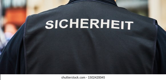 """Back view of a guard with a black waistcoat with the German inscription """"Sicherheit"""" (Translation: security)"""
