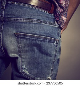 Back view of a guy wearing a denim against grey background