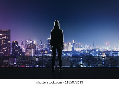back view of hacker in sport suit standing on roof top above night megapolis city