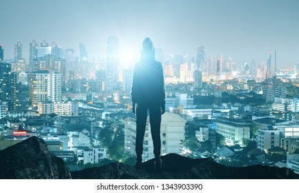 Back view of hacker standing on top of hill with night city background. Vision and purpose concept
