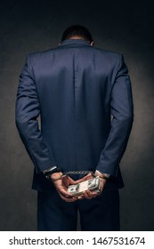back view of handcuffed man in suit holding bribe on grey