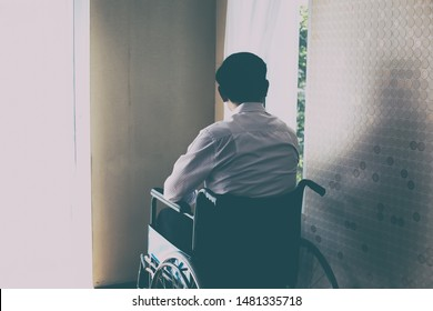 Back view of handicapped Man sitting on wheelchair in front of a large panoramic window in hospital,He is sad and lonely.