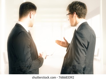 Back view of handsome european businessmen discussing contract in blurry bright office. Teamwork and finance concept. Double exposure
