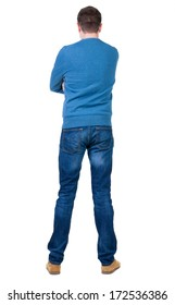 Back view of handsome man in blue pullover looking up.   Standing young guy in jeans. Rear view people collection.  backside view of person.  Isolated over white background.