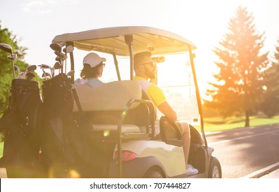 Back view of handsome men driving a golf cart