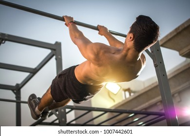 Back view of handsome shirtless man exercising on horizontal bar outdoors. Calisthenics workout.