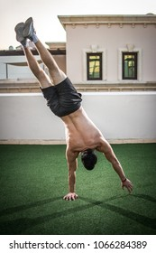 Back view of handsome shirtless man doing handstand on one hand outdoors
