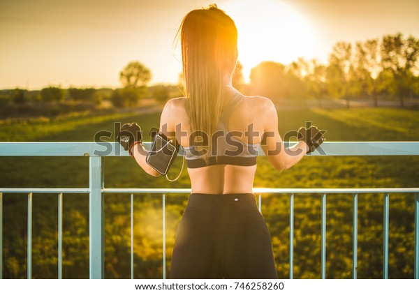 Back view of handsome sporty woman enjoying the view over the bridge at sunset.