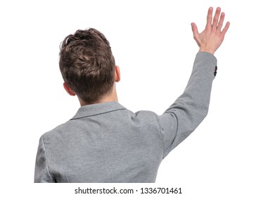 Back view of Handsome Teen Boy in gray suit stretching his right hand up for greeting. Portrait of caucasian Teenager waving hand isolated on white background.