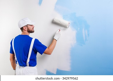 Back view of handsome young painter in white dungarees, blue t-shirt, cap and gloves painting a wall with paint roller.