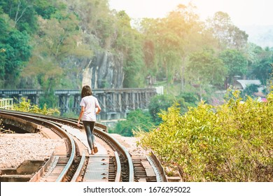Back view of happiness girl walking on Krasae cave and The Death Railway bridge Thai to Myanmar over the Kwai Noi River in World War II.