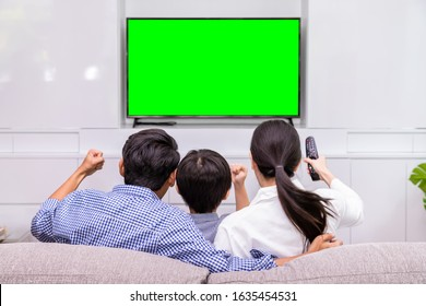 Back view of happy Asian family watching TV together in living room at home; cheerful and fun with movie, with green screen