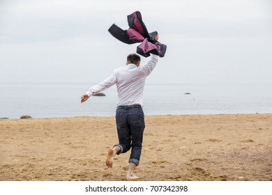 Back view. Happy businessman in white shirt and jeans with a jacket in his hand overhead runs along the sand barefoot. Man quit his job and enjoys freedom or celebrates successful deal. Film effect.