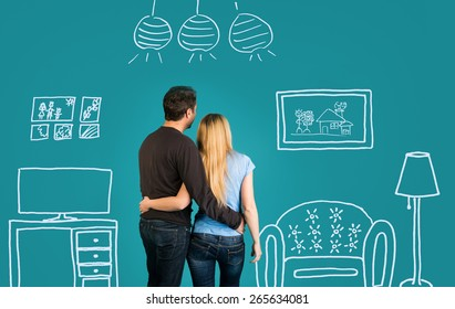 Back view Of Happy Couple Dreaming Of Their New Home And Furnishing On Blue Background. Family With Sketch Drawing Of Their Future Flat Interior.