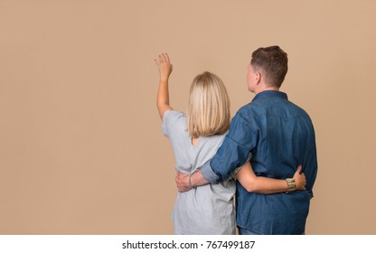Back view Of Happy Couple Dreaming Of Their New Home And Furnishing On Beige Background.