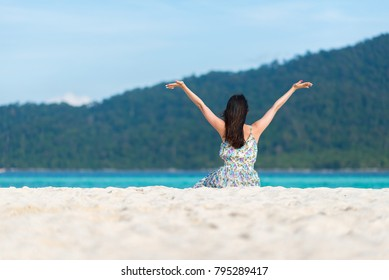 Back view of  happy delightful young woman enjoying a day at the beach