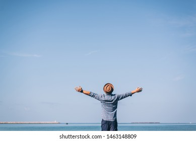 Back view of Happy excited man winner traveler or hipster raising arms up to blue sky feeling free motivated over the beach enjoying beautiful view travel on vacation, freedom concept