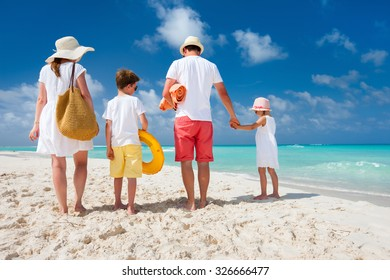Back view of a happy family with kids on tropical beach vacation