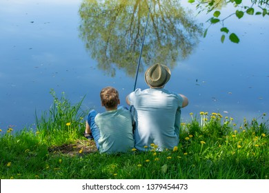 Back view of happy family on summer vacations concept. Father and son fishing together at river bank at scenic landscape background of fresh green grass and blue calm water.