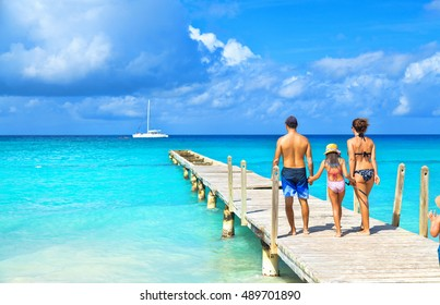 Back view of a happy family on tropical beach. Family standing on a wooden pier.