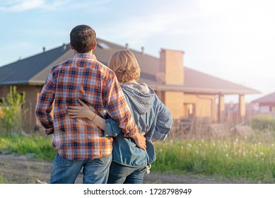 Back view of happy family is standing near their new modern house and hugging