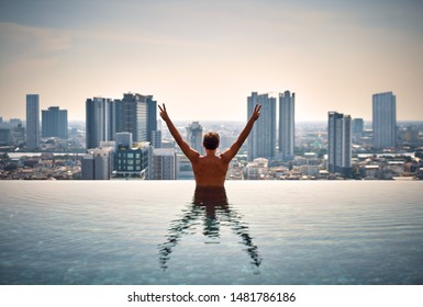 Back view of happy freedom man with raised arms enjoy his summer vacation on swimming pool on roof top of hotel. Travel, holidays, success concept