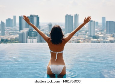 Back view of happy freedom woman with raised arms enjoy her summer vacation on swimming pool on roof top of hotel. Travel, holidays, success concept