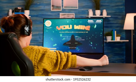 Back view of happy pro gamer winning space shooter game, raising hand celebrating, Virtual shooter game in cyberspace, esports player playing on computer video game sitting at home, gaming tournament