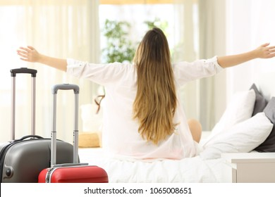 Back view of a happy traveler celebrating vacations sitting on a bed in an hotel room at arrival with suitcases in foreground