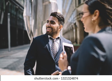 Back view of happy Turkish male banker laughing from funny joke of female colleague and enjoying work break togetherness, positive economists smiling outdoors while talking about conference