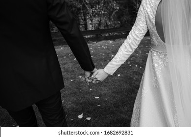 Back view of happy wedding couple walking on garden, copy space. Close up of young bride and groom walking outdoors. Beautiful relationship.
