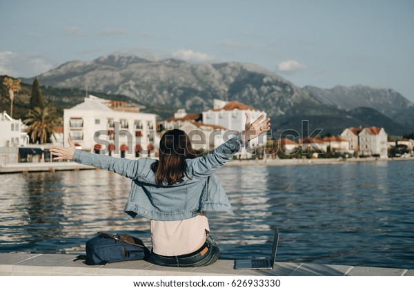 Back view of happy woman raised hands sitting on Embankment with laptop. Vacations, freelancer, lifestyle