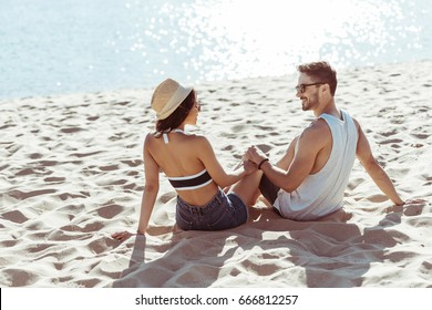 Back view of happy young couple holding hands while sitting on sandy beach
