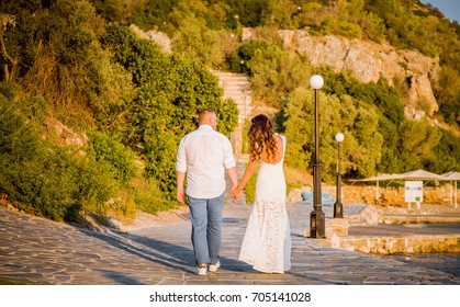 back view of happy young couple in white on the prominade