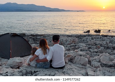 Back view of happy young family, sitting on rock beach near tent and admiring setting sun over sea. Mom, dad and little daughter embracing and having great time together. Concept of friendly family.