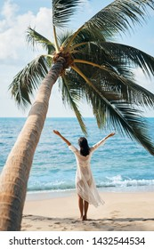 Back view of happy young woman enjoy her tropical beach vacation standing under palm tree. Summer concept