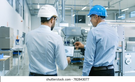 Back View of the Head of the Project Holds Laptop and Discussing Product Details with Chief Engineer while They Walk Through Modern Factory.