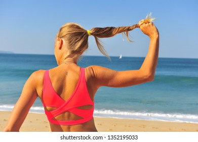 Back view of healthy woman holding her strong hair on the beach