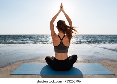 Back view of healthy young sport woman practicing yoga sitting in padmasana at seaside