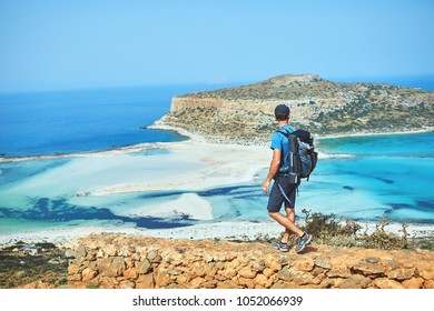 back view of hiker with small backpack on the trail to the Balos beach at early morning. Balos beach on background, Crete, Greece