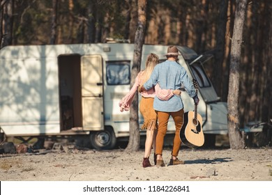 back view of hippie couple hugging and walking with acoustic guitar near campervan