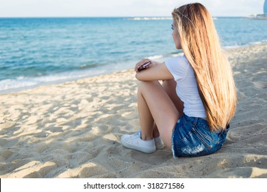 Back view of hipster girl holding cell telephone while sitting alone on the beach enjoying sea landscape in summer day,dreamy woman waiting for a call on her smart phone while relaxing after promenade
